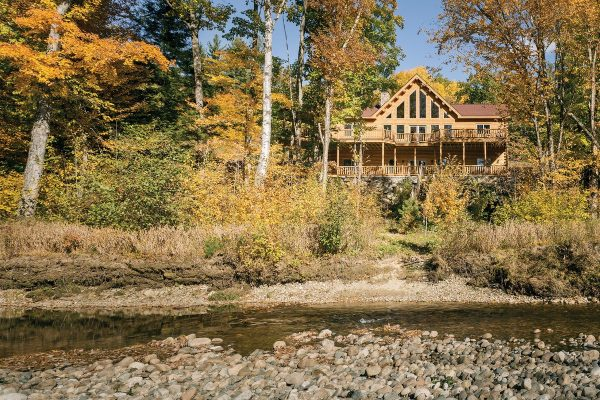 Exterior of multi level log home alongside the creek