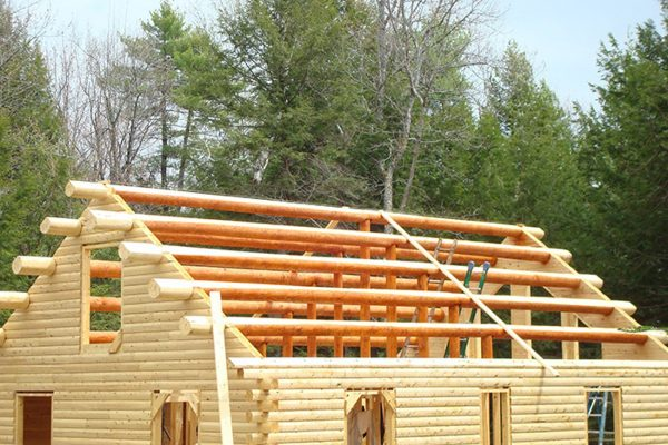 The roof is ready to be installed on this handmade log cabin.