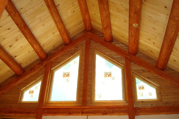 Exposed wooden ceiling beams made from whole logs give this cabin a handmade look.