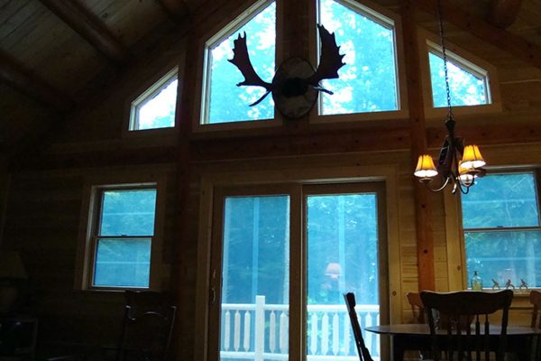 Moose antlers loom intriguingly over transom windows in a log cabin.