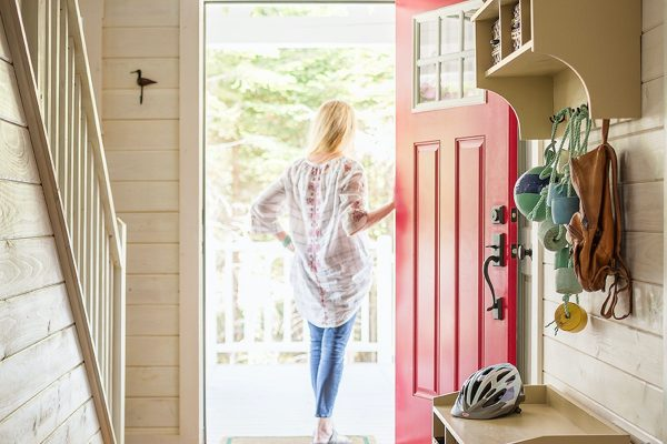 A woman standing in the doorway of her new home.