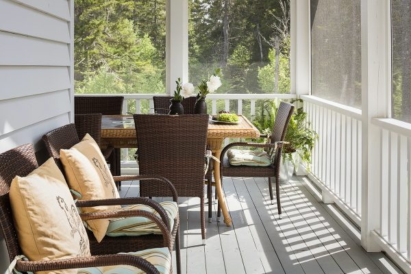 Outdoor furniture on a screened in porch.