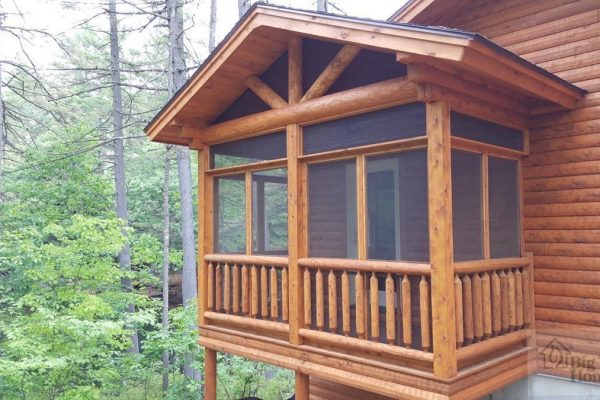 A screened in porch on a log home.