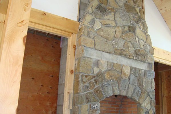 A Stone fireplace that reaches to the top of a vaulted ceiling.