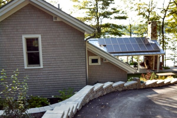 Sun room with solar panels on the roof viewed from driveway