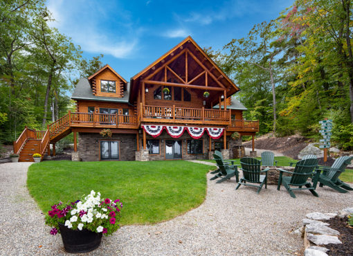 exterior view of cedar log home with fire pit and chairs in foreground