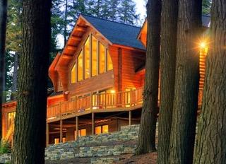 exterior shot of cedar log home framed by trees