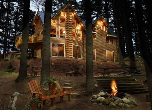 exterior shot of log home at night with chairs and fire pit in foreground