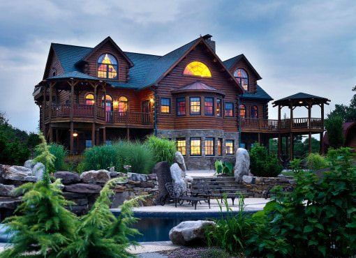 exterior shot of log home at dusk with swimming pool in foreground